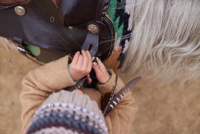Overhead view of a girl in a winter coat adjusting the leather saddle rigging