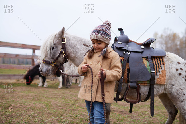 Girl in a winter overcoat standing next to a pony