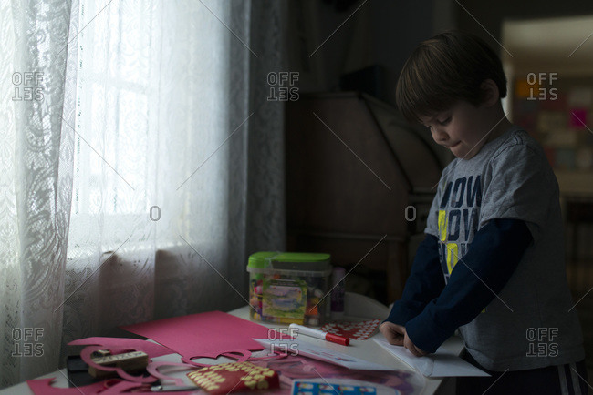 Boy making art on table by the window