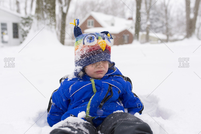 Boy sitting in snow and pouting with a snow covered hat