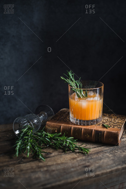 Orange cocktail garnished with rosemary sprig sitting on an old book