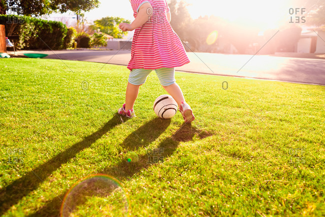 Girl kicking a soccer ball in the yard
