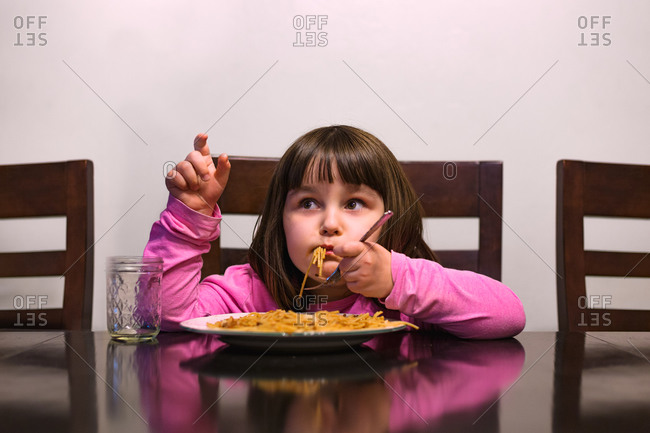 Girl eating spaghetti while sitting at the table