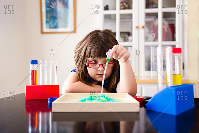 Girl holding a pipette while working on a science experiment at home