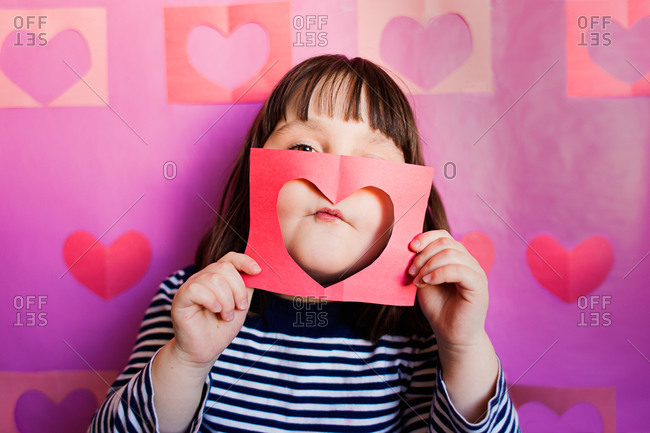 Girl holding a cut out heart to her face