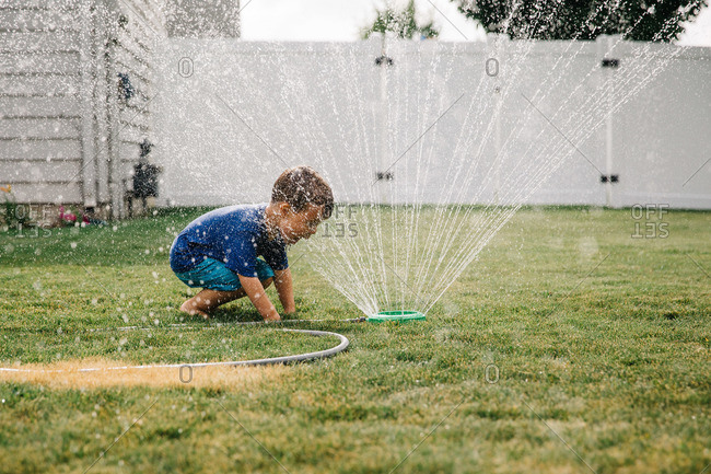 Boy playing with a sprinkler in the yard