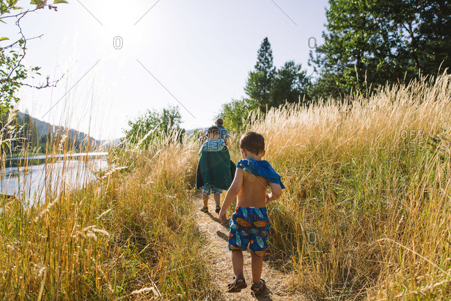Two boys in wet bathing suits walking along a grassy path behind their father