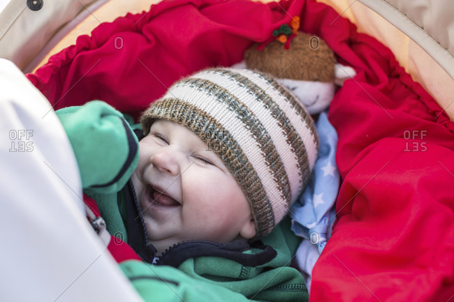 95de826d8 Portrait of laughing baby boy wearing woolly hat stock photo - OFFSET