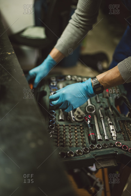 Young mechanic taking tool from tool box, close up