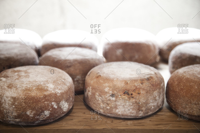 Round wheels of aging cheese on a wooden table