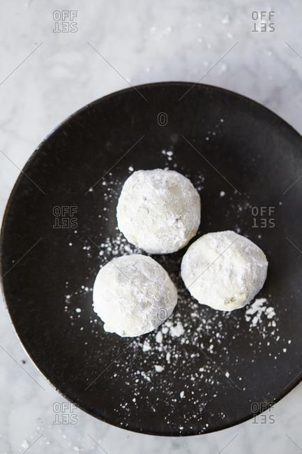 Sesame balls coated in powdered sugar on a black plate