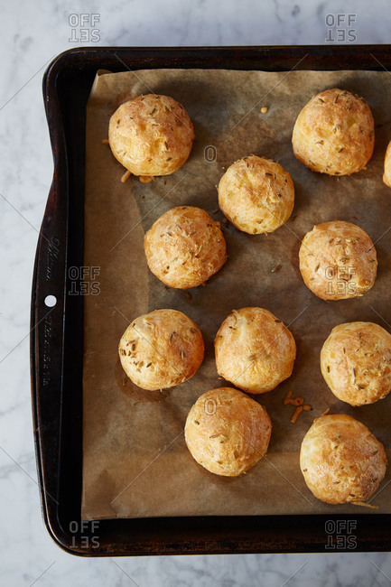Fresh baked cheese puffs cooling on a baking pan