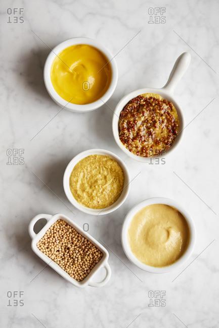 Variety of mustard in white ceramic dishes