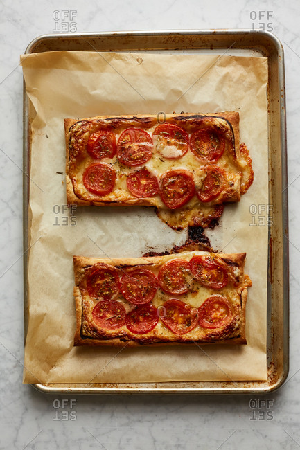 Tomato tarts with gooey cheese on a baking sheet