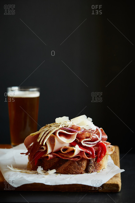 Open-faced Italian sandwich with various lunchmeats and a pint of beer