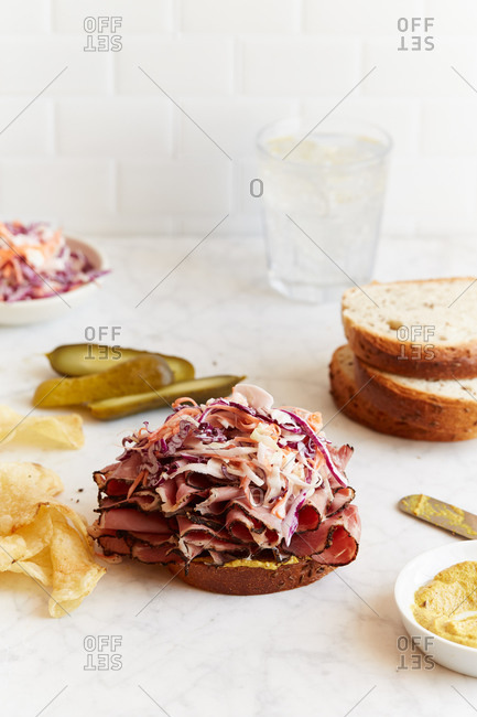 Open face sandwich with pastrami, coleslaw and pickles