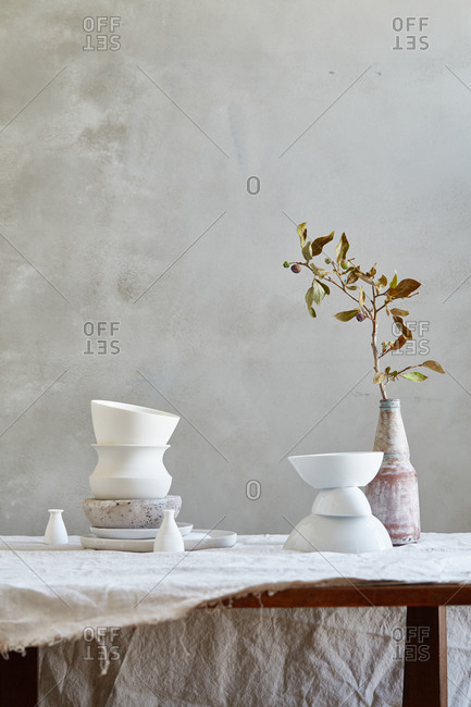 White ceramics, fig branch and muslin cloth on a table