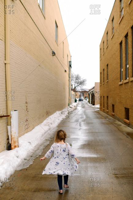 Little girl walking down an alley