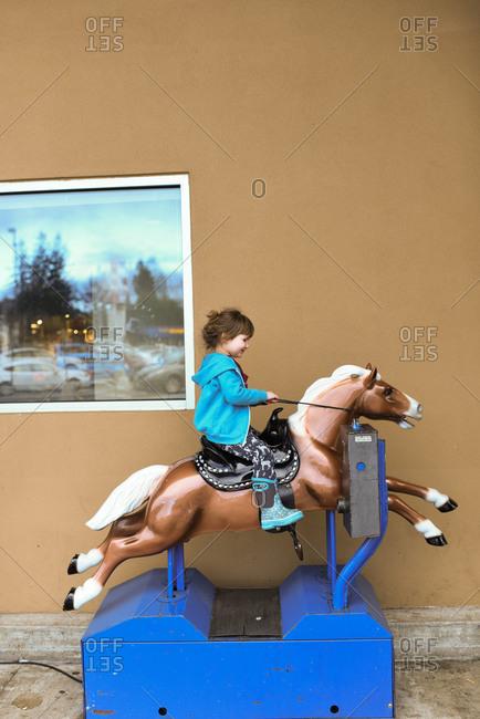 Little girl riding a mechanical horse ride