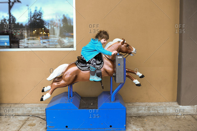 Little girl inserting money to ride a mechanical horse ride