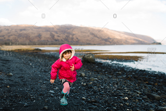 Little girl running beside a mountainside lake