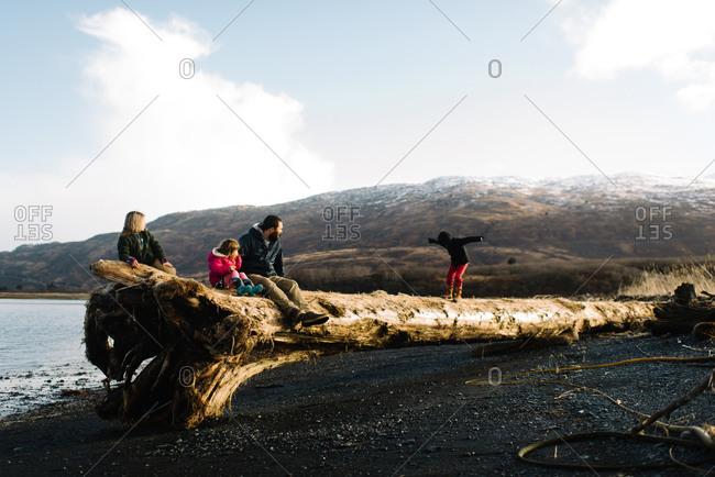 Boy walking across fallen tree while family sits on it