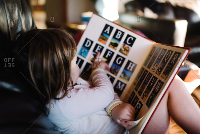 Close up of little girl reading a letter book