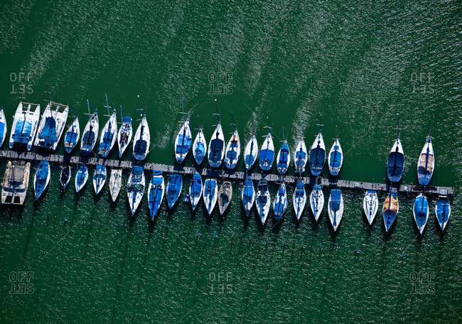 Sailboats moored along a long wooden dock