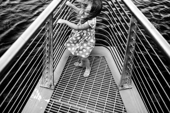 Black and white image of girl standing at the front of a boat
