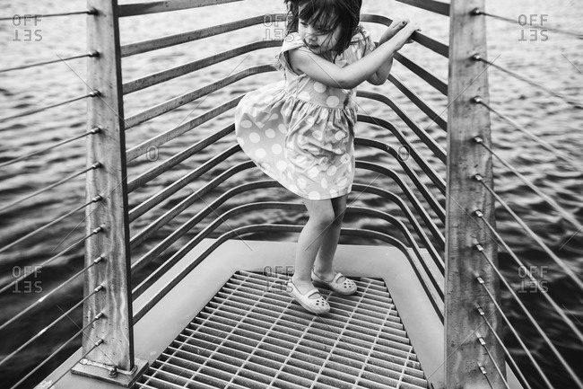 Girl standing at the front of a boat in a polka dot dress
