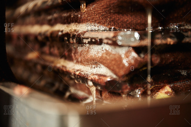 Close up of cider press, layers of apple pulp being pressed, extracting juice