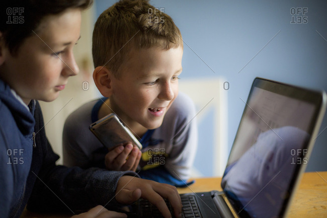 Two boys playing on a laptop computer