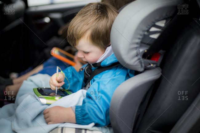 Boy in the backseat of a car using digital device