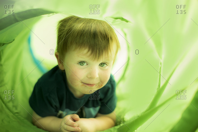 Smiling young boy crawling through green tunnel