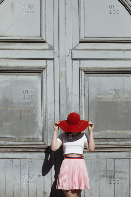 Young woman in a red hat standing in front of a gray exterior wall