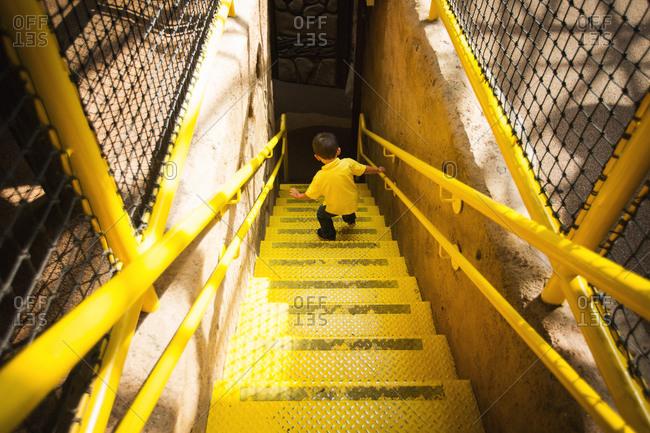 Boy walking down a yellow staircase