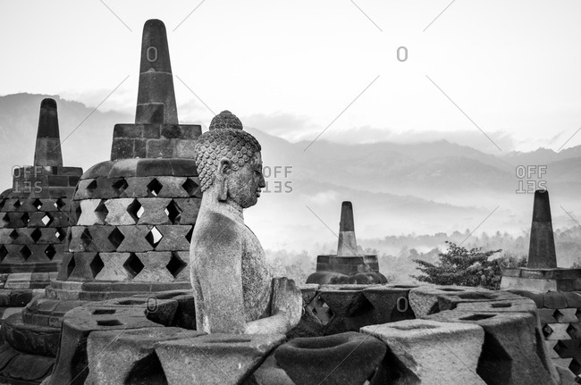 Buddha statue and stupas at a temple in Java, Indonesia