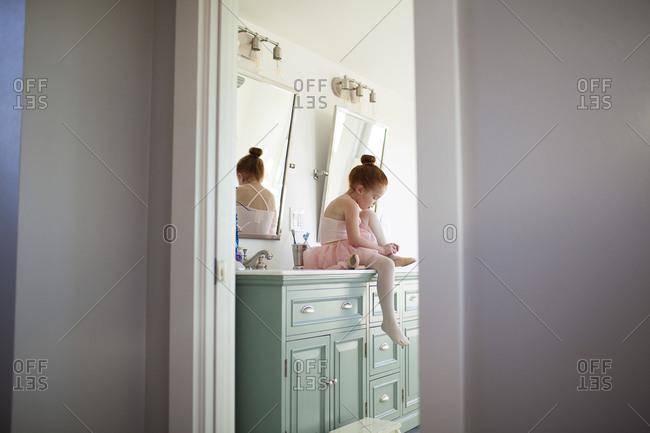 Little girl sitting on a bathroom vanity putting on ballet slippers