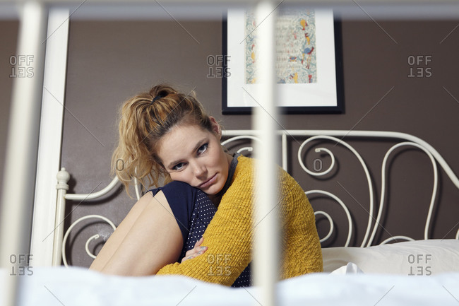 Woman sitting on a bed hugging her knees