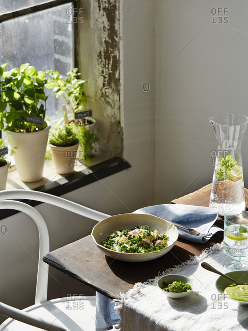 Small table near a window set with a healthy salad and pitcher of water