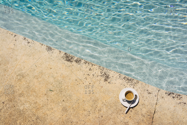 Cup of espresso sitting on the edge of a pool
