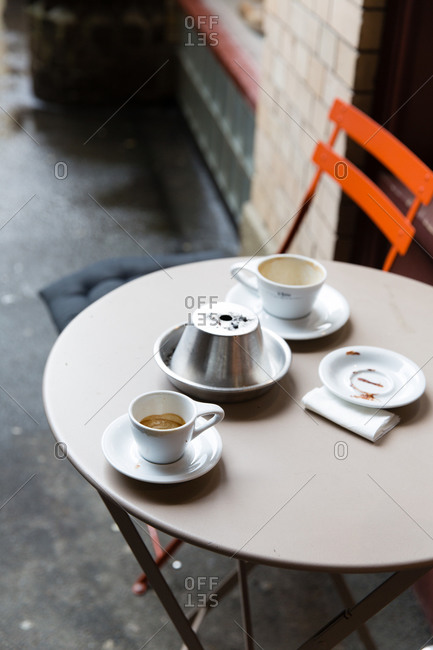 Cafe table on the sidewalk with empty espresso cups and dishes