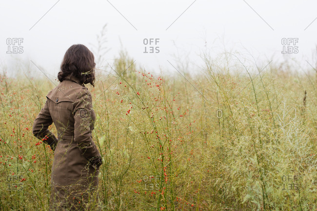 Woman standing in a field of tall wild grass