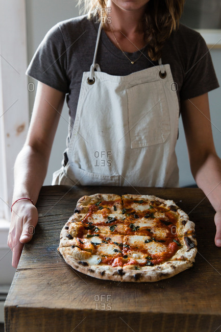 Woman holding a wood board with an artisanal pizza