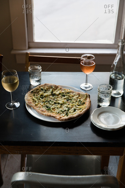 A table set with artisanal pizza, wine, and water