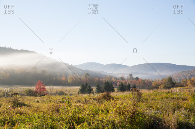A morning mist settling over a field in a mountain valley
