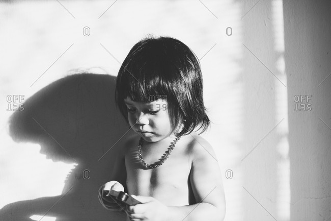 Boy against wall examining toy