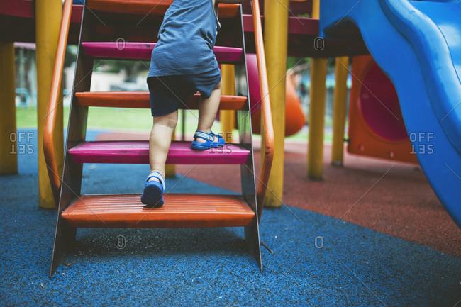 Feet of boy climbing playground equipment