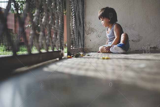 Boy on front patio with toys