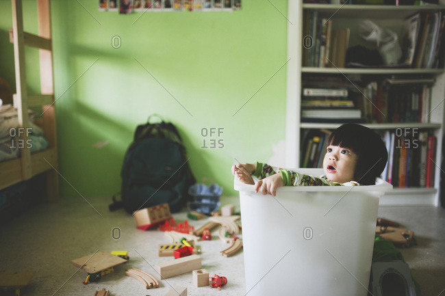 Boy looking up in a plastic tub